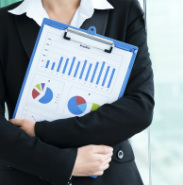 A photograph of a woman holding a clipboard with financial graphs and pie charts on the front.