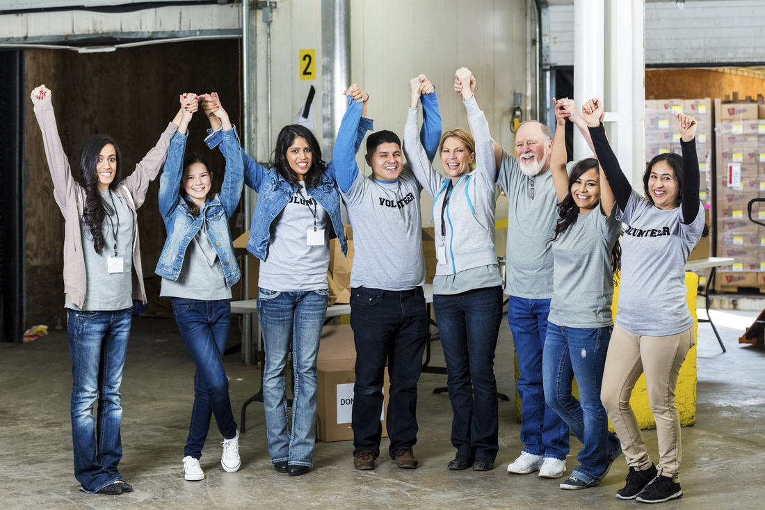 A group of eight volunteers at a food pantry sorting facility who have all joined hands and raised them above their heads in a happy cheer. All of them are wearing tee shirts that say