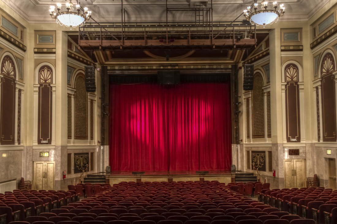 A photograph of the inside of an old theater facing the proscenium stage with a velvet curtain.