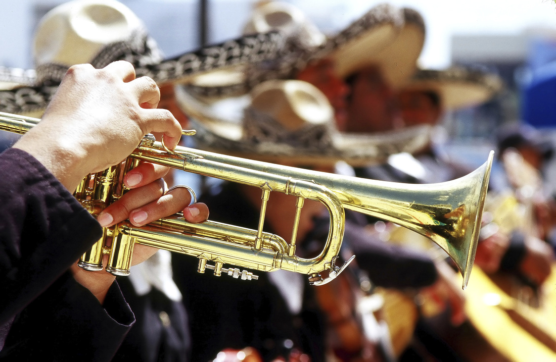 A photograph of a mariachi bank and a close of of a musician playing a trumpet