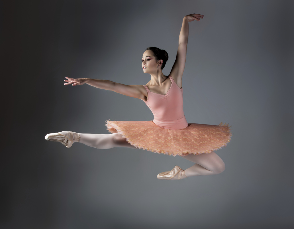 A ballet dancer in a tutu in mid air jumping.