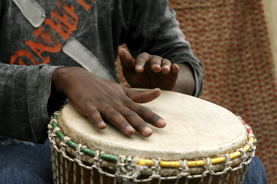 A photograph of a man playing an African drum